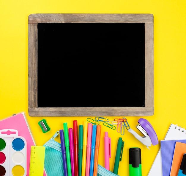 Lay flat de elementos esenciales de la escuela con acuarela y pizarra