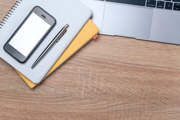 Lay flat de escritorio de oficina de madera con laptop, bolígrafo y cuaderno con copia espacio de fondo.