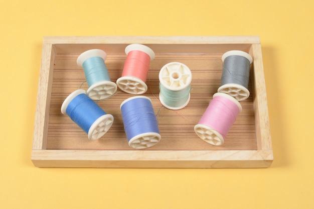 Lay flat de hilos de colores rollos para coser sobre fondo amarillo