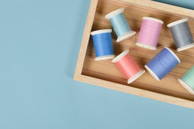 Lay flat de hilos de colores rollos para coser sobre fondo azul