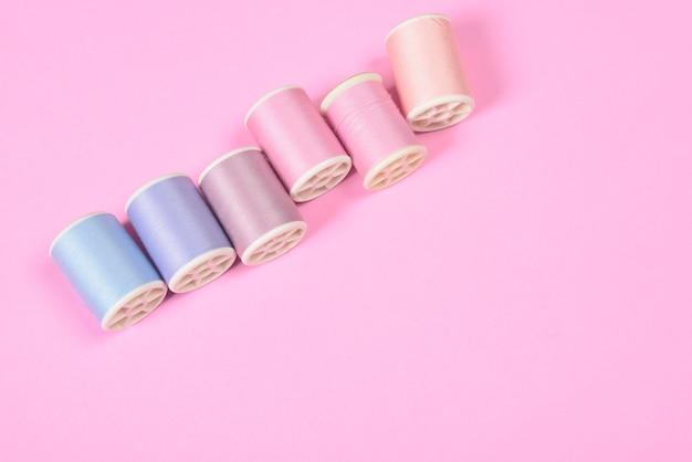 Lay flat de hilos de colores rollos para coser sobre fondo rosa