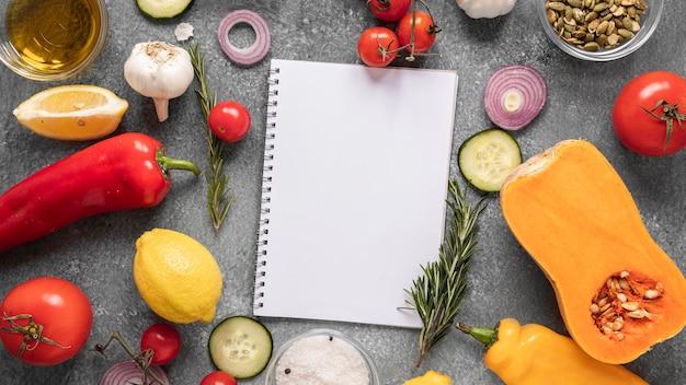 Lay flat de ingredientes alimentarios con cuaderno y verduras
