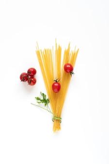 Lay flat de ingredientes de espaguetis crudos dispuestos como un ramo sobre la superficie blanca