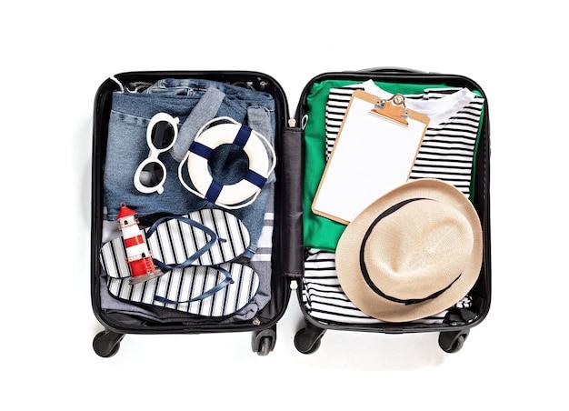Lay flat con maleta abierta con ropa casual para vacaciones de verano sobre pared blanca. vacaciones de verano, viajes, turismo, concepto de equipaje de vuelo. vista superior