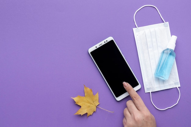 Lay flat de mano con smartphone con máscara médica y hoja de otoño