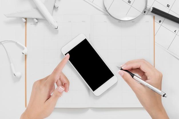 Lay flat de manos de mujer usando teléfono inteligente y escribiendo en plan de itinerario de viaje con espacio en blanco
