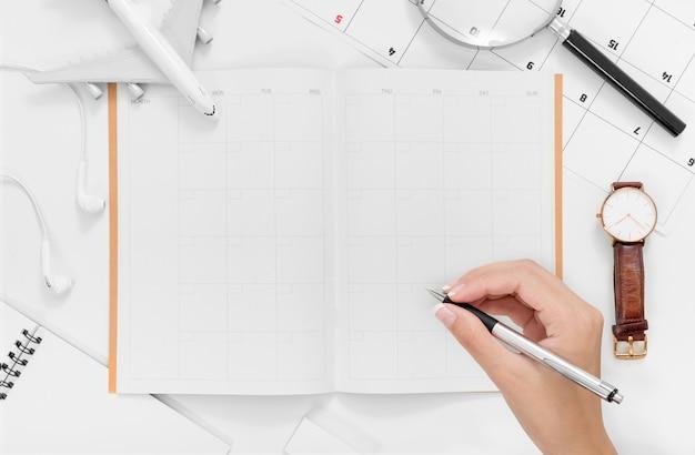 Lay flat de mujer manos escribiendo en plan de itinerario de viaje con espacio en blanco