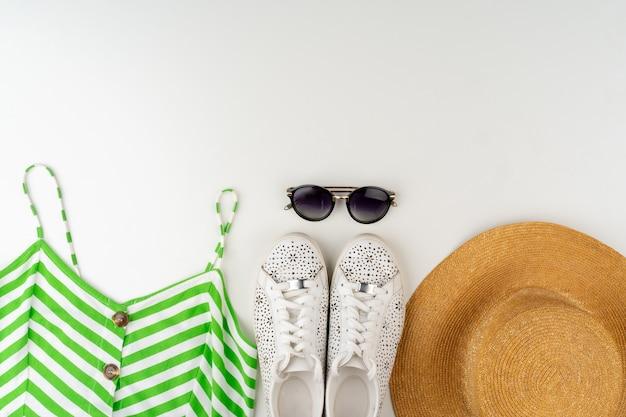 Lay flat de mujer traje de verano sobre fondo blanco.