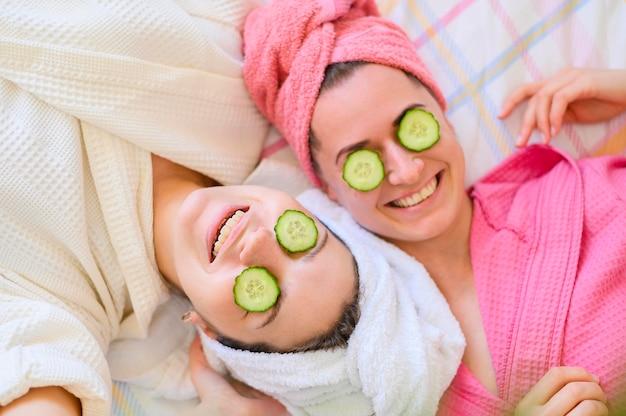 Lay flat de mujeres sonrientes con rodajas de pepino en los ojos
