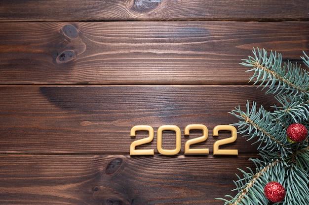 Lay flat de números 2022, ramas de abeto, bolas rojas, fondo de madera.