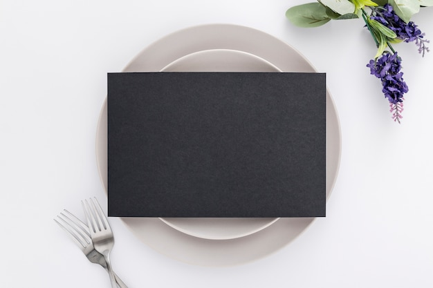 Lay flat de papel de menú en blanco en platos con tenedores y flores
