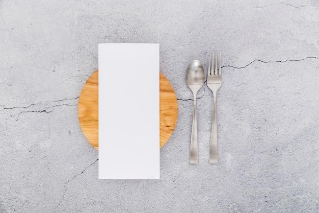 Lay flat de papel de menú en blanco sobre hormigón con cubiertos