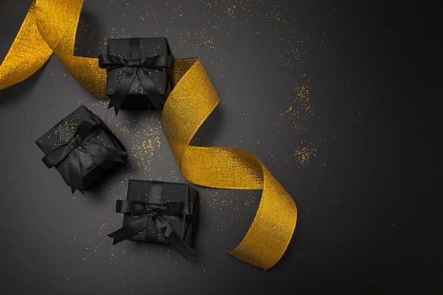 Lay flat de regalos de navidad oscuros con cinta dorada