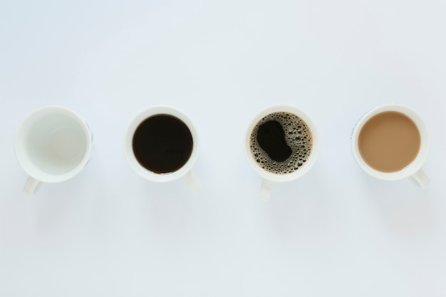 Lay flat de tazas de café en la mesa blanca