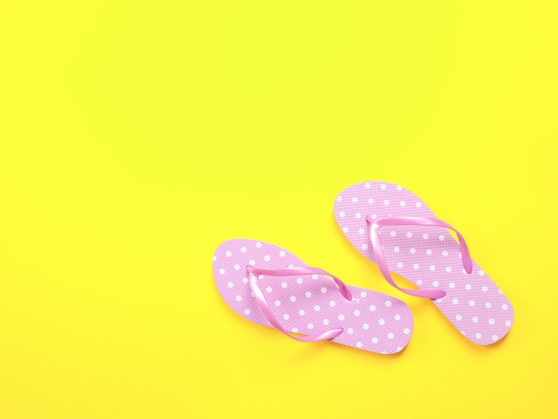 Layout de verano. chanclas y gafas de sol rosadas de los accesorios de la playa en fondo amarillo.