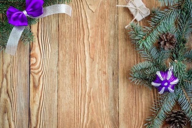 Lazo y cinta decorativos de color púrpura. composición de navidad con ramas de abeto. conos, cuentas y bolas sobre tabla de madera con espacio de copia.