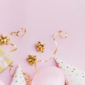 Lazo de cinta dorada; serpentinas caja de regalo; globos y sombrero de fiesta sobre fondo rosa.