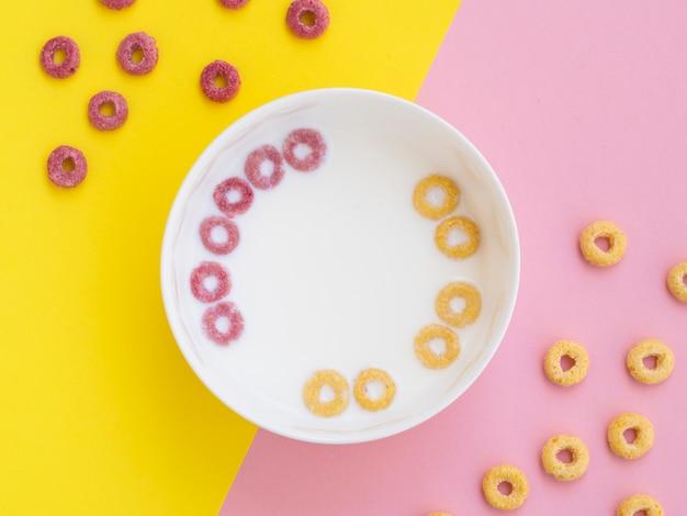 Lazos de cereales de fruta rosa y amarilla en un tazón
