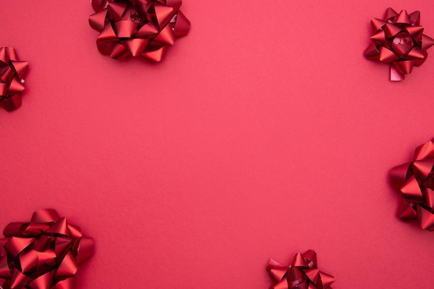 Lazos de cinta roja sobre fondo rojo, endecha plana.