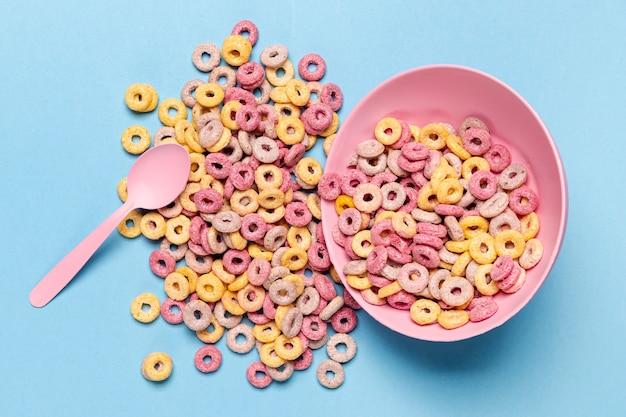 Lazos de fruta de cereal derramado de un tazón rosa