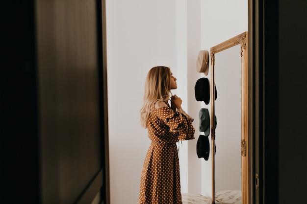 Lazos de mujer joven se inclinan sobre su elegante vestido. chica mira en el espejo antes de ir a una cita romántica.