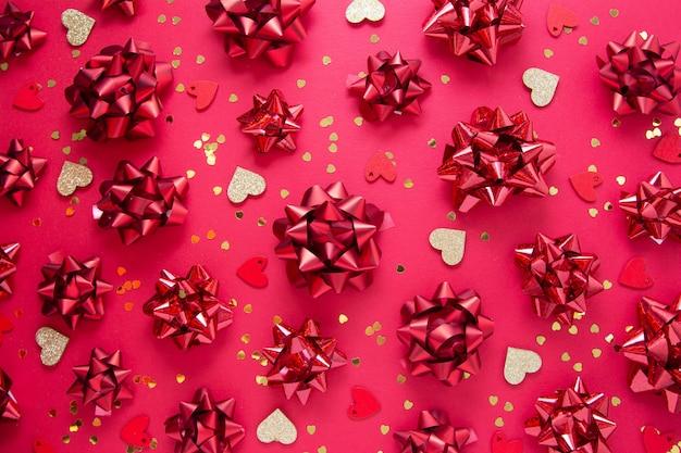 Lazos rojos, brillo dorado en forma de corazón sobre rojo