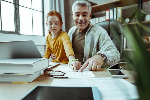 Lección casera. buen hombre positivo sosteniendo a su hija en sus regazos mientras la ayuda a leer