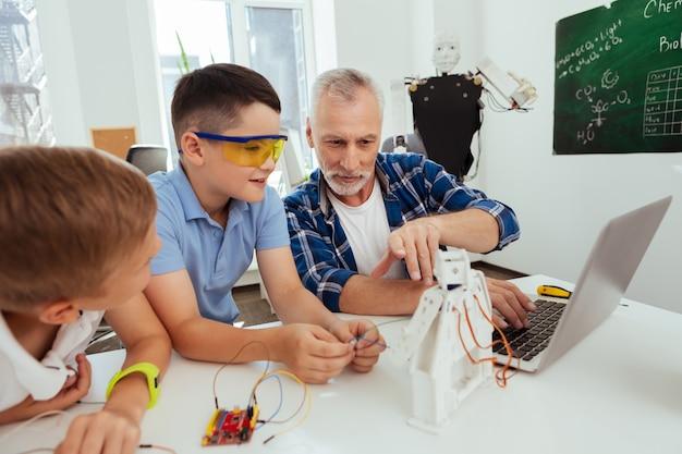 Lección de ciencia. profesor inteligente alegre sentado junto con sus alumnos mientras les habla de robots