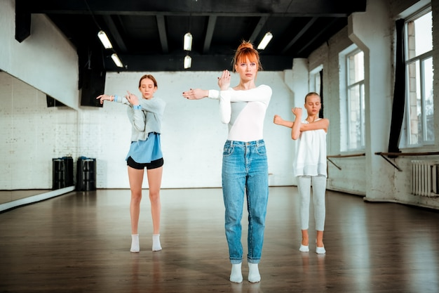 Lección de danza moderna. profesora de danza moderna profesional con cabello rojo que parece serio mientras muestra movimientos a sus alumnos