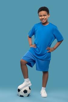 Lección, fútbol. alegre niño de piel oscura en camisa deportiva azul y pantalones cortos sosteniendo la pelota con el pie de muy buen humor