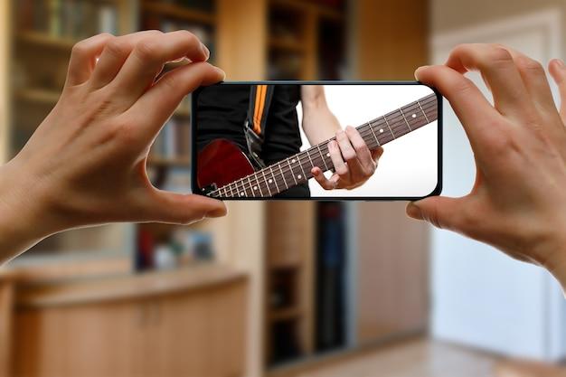 Lección de guitarra en línea a través de un teléfono inteligente.