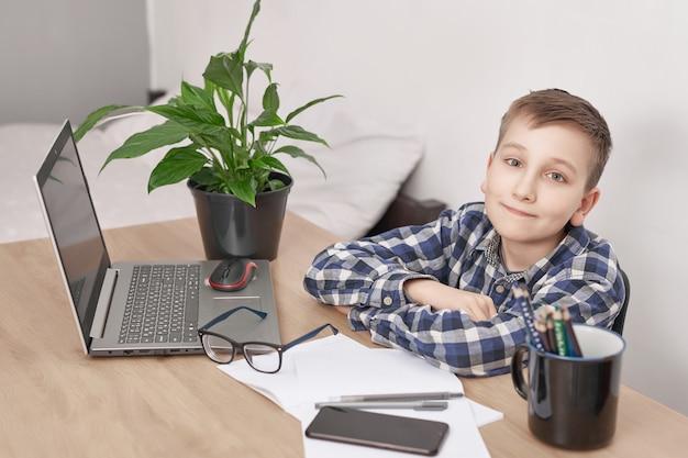 Lección en línea en el hogar, distancia social durante la cuarentena, autoaislamiento, concepto de educación en línea, educación en el hogar. niño aprendiendo idiomas en línea, usando una computadora portátil, educación a distancia. estudiante chico, escuela