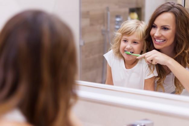 Lección matutina de cepillarse los dientes con mami