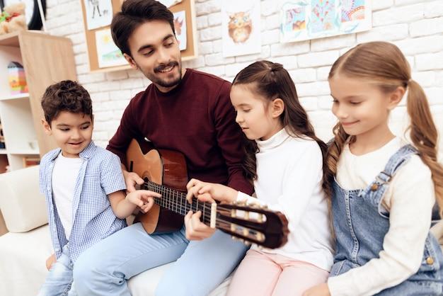 Lección de música para niños sobre cómo tocar la guitarra.