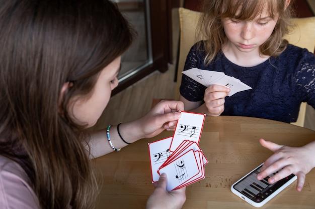 Lección de teoría musical, solfeo usando la aplicación de piano en su teléfono y tarjetas educativas