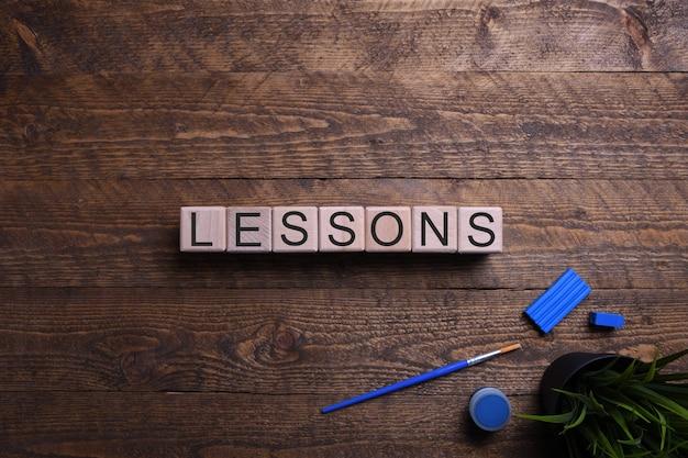 Lecciones de palabras sobre cubos de madera, bloques sobre el tema de la educación, el desarrollo y la formación en una mesa de madera. vista superior.