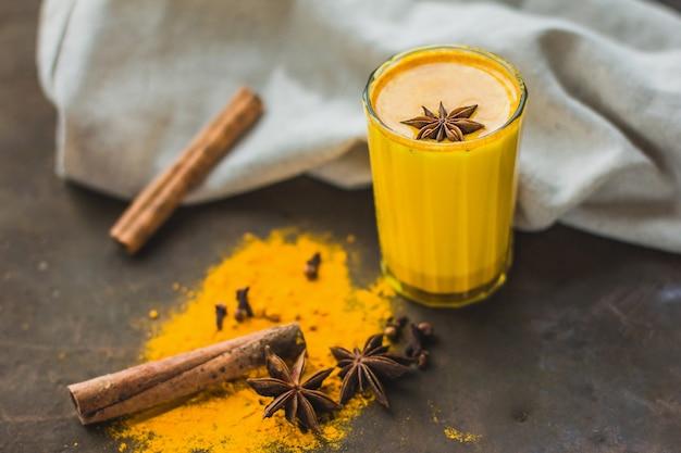 Leche de almendras doradas o café con leche de calabaza y cúrcuma con cúrcuma en polvo sobre un fondo oscuro de cerca. bebida detox natural asiática de moda con especias para veganos