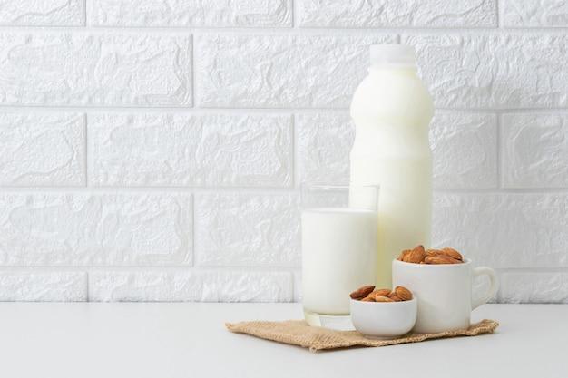 Leche almendras en un vaso sobre blanco