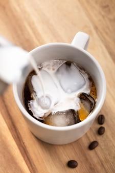 Leche de alto ángulo vertida en café helado