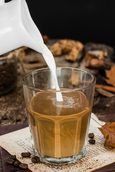Leche de alto ángulo se vierte en vaso con café