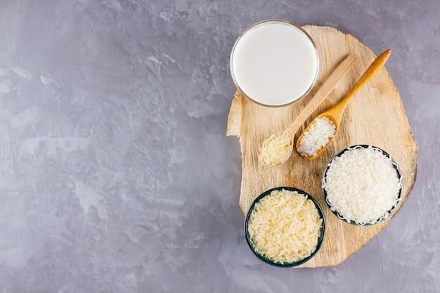 Leche de arroz y semillas de arroz sobre fondo gris