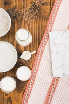 Leche; azúcar; molde de harina y pastel con lista de tareas sobre tela texturizada sobre mesa con textura de madera