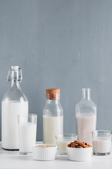 Leche en botellas y vasos con avena y almendras.