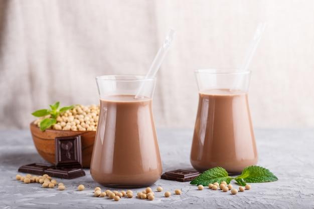 Leche de chocolate de soja orgánica no láctea en vidrio y placa de madera con soja sobre un fondo de hormigón gris