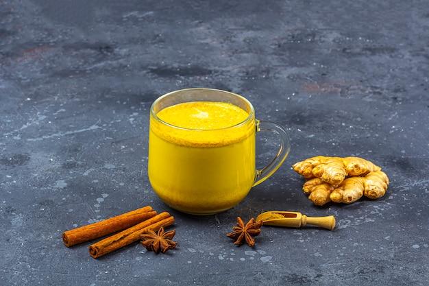 La leche de cúrcuma de bebida india tradicional es leche dorada en una taza de vidrio con cúrcuma y raíz de jengibre, canela, anis estrella sobre fondo oscuro. pérdida de peso, bebida saludable y orgánica. de cerca