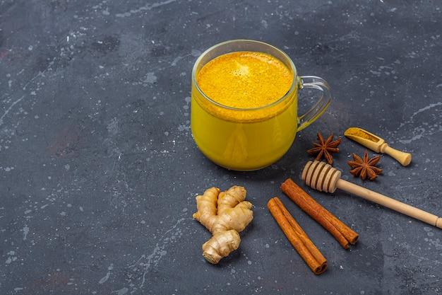 La leche de cúrcuma de bebida india tradicional es leche dorada en una taza de vidrio con cúrcuma y raíz de jengibre, canela, anís estrella sobre fondo oscuro. pérdida de peso, bebida saludable y orgánica.