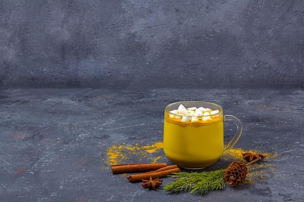 Leche de cúrcuma india tradicional en taza de vidrio con canela, malvaviscos y piñas