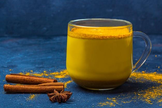 Leche de cúrcuma india tradicional en taza de vidrio con estrella de anís y canela