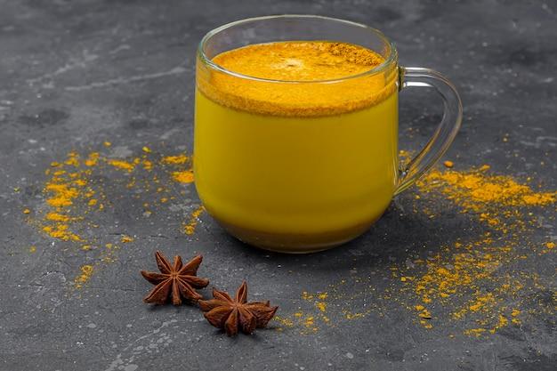 Leche de cúrcuma india tradicional en taza de vidrio con estrella de anís