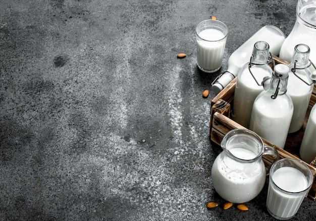 Leche fresca en botellas y jarras con caja de madera. sobre un fondo rústico.